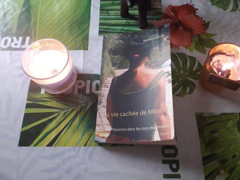 Roman la vie cachée de Mina M posé sur une table entre deux bougies.