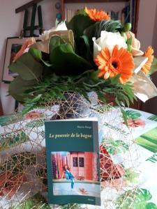 Le roman Le pouvoir de la bague posé sur une table avec un bouquet de fleurs.